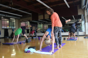 Personal attention to proper form in a Mind Body Yoga Class